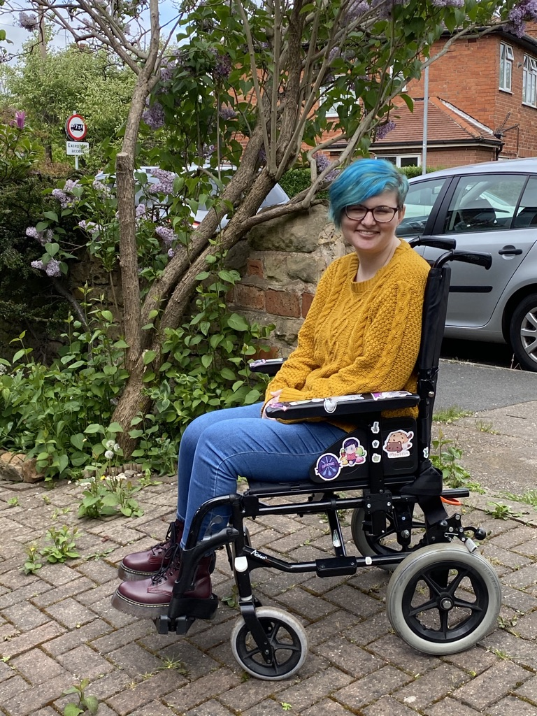 Jase is a non-binary person in a yellow jumper and blue jeans sitting in a wheelchair in their front drive
