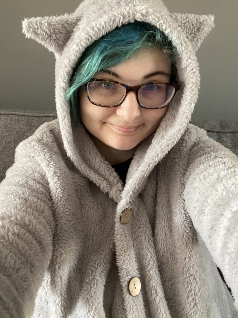 Jase is wearing a fluffy grey cardigan with cat ears