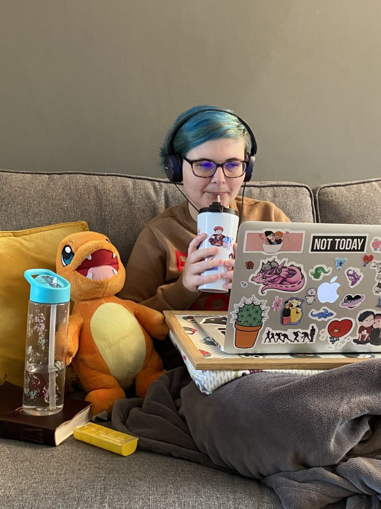 Jase is sitting on a sofa under an electric blanket, holding a hot drink, using her laptop. There is a charmander plush and a water bottle beside them.