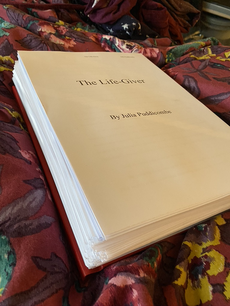 A large pile of paper titled 'The Life-Giver' by Julia Puddicombe (Julia is Jase's birth name)
