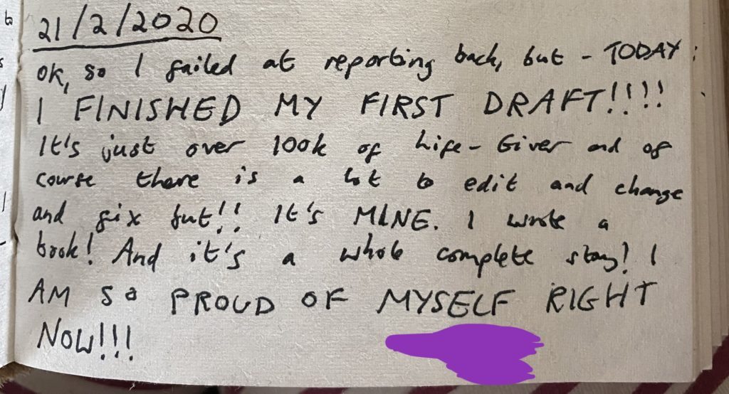 Handwritten text in a journal dated 21/2/2020. The text reads: 'Ok, so I failed at reporting back, but - TODAY I FINISHED MY FIRST DRAFT!!!! It's just over 100k of Life-Giver and of course there is a lot to edit and change and fix but!! It's MINE. I wrote  a book! And it's a whole complete story! I AM SO PROUD OF MYSELF RIGHT NOW!!!