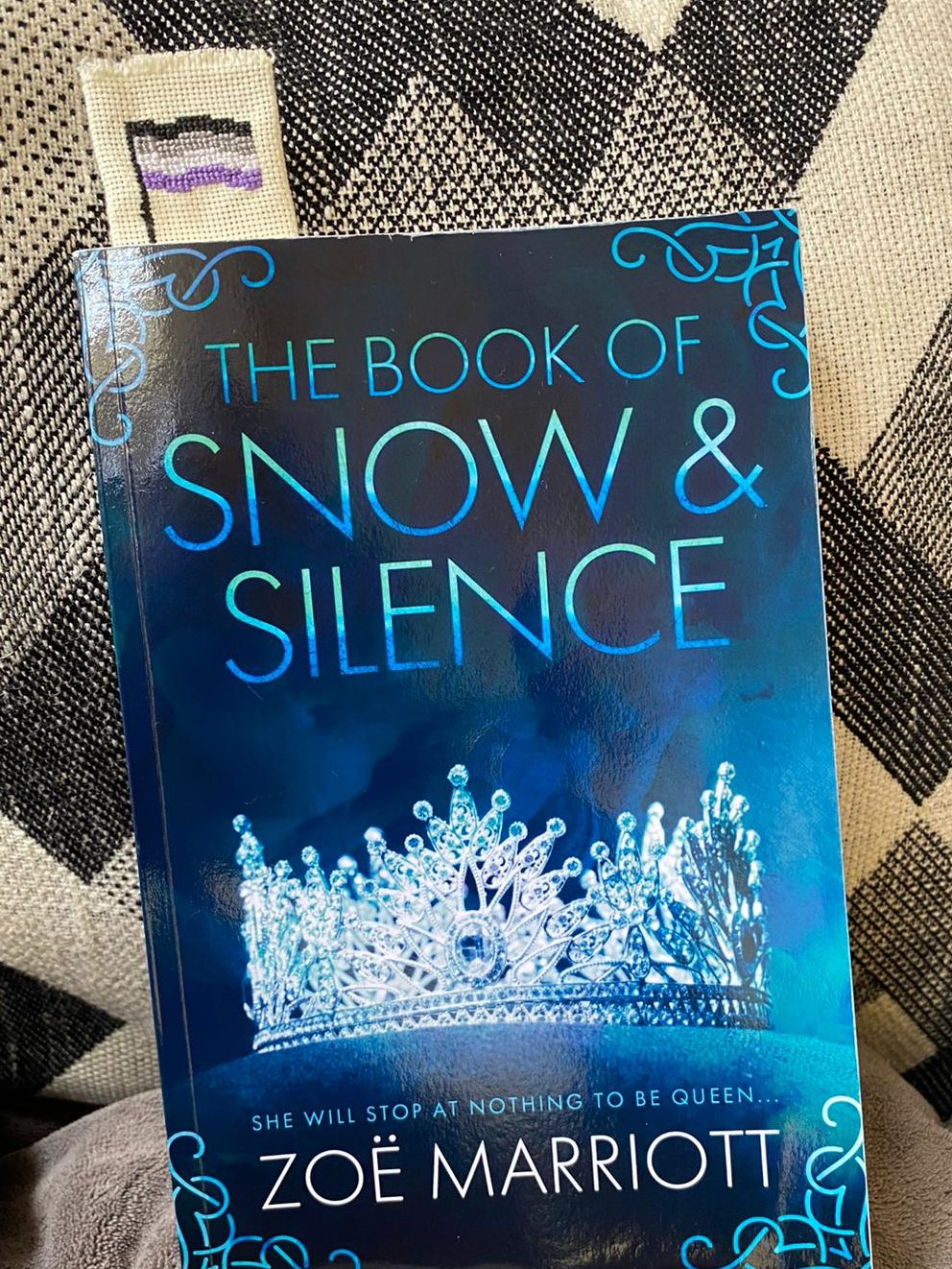 A photo of the Cover of the Book of Snow and silence. It is dark blue with lighter blue writing and white frost-like images