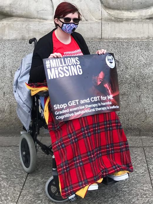 Jase is sitting in their wheelchair holding a sign that says Millions Missing: Stop CBT and GET for ME